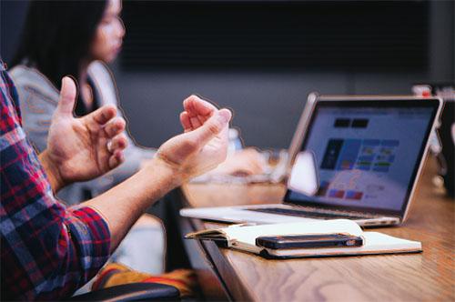 persona sentada en una mesa con un teléfono y un ordenador portátil