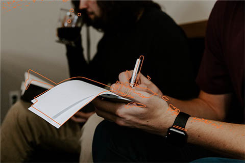 personne écrivant sur une feuille