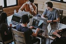 quatre personnes devant leurs ordinateurs
