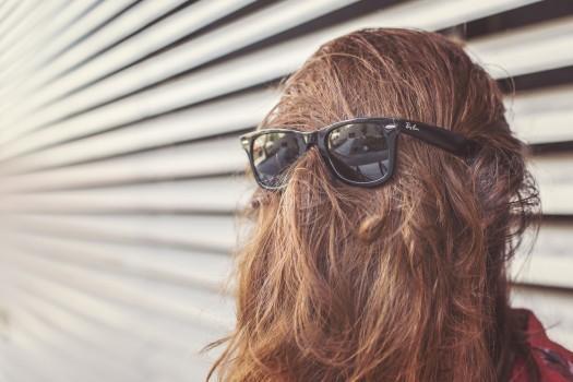 tête de femme vue de dos,avec des lunettes de soleil